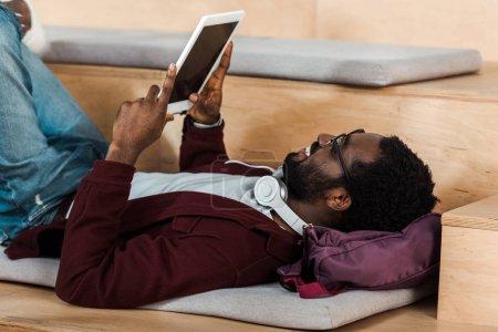Photo pour Étudiant afro-américain couché sur le sac à dos et en utilisant la tablette numérique à l'université - image libre de droit
