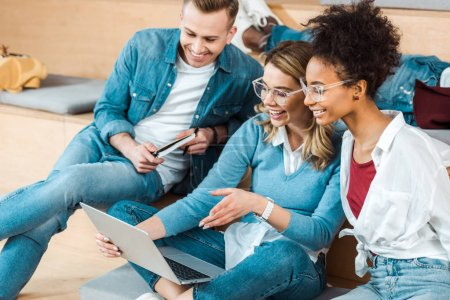 Photo pour Étudiants multiculturels souriants utilisant un ordinateur portable dans la salle de conférence - image libre de droit