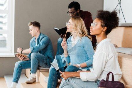 Photo pour Étudiants multiculturels avec cahiers et ordinateur portable dans la salle de conférence - image libre de droit