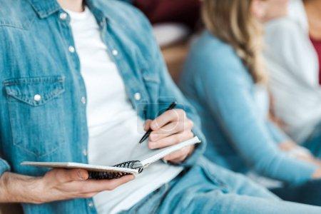 Photo pour Vue recadrée de l'étudiant en denim chemise tenant stylo et cahier - image libre de droit