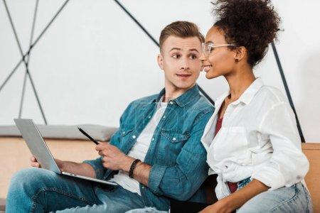 Photo pour Deux étudiants multiethniques gais utilisant l'ordinateur portatif à l'université - image libre de droit
