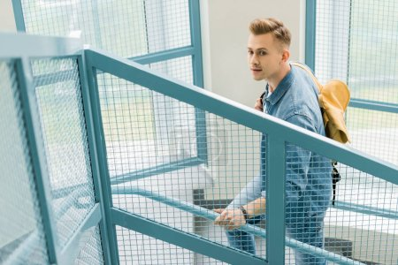 Photo for Student in denim shirt with yellow backpack on stairs in university - Royalty Free Image