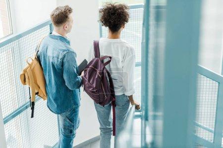 Photo pour Vue arrière de deux étudiants internationaux avec des sacs à dos - image libre de droit
