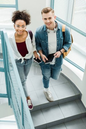 Photo for Overhead view of two students with notebook and smartphone standing on stairs - Royalty Free Image