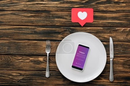 Photo for Top view of smartphone with instagram app on screen near knife, fork and red paper cut card with heart symbol on brown wooden surface - Royalty Free Image