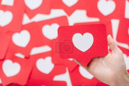 Photo for Cropped view of female hand with red paper cut card with heart symbol - Royalty Free Image