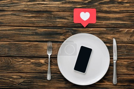 Photo for Top view of  smartphone with blank screen on white plate near knife, fork and red paper cut heart with heart symbol on brown wooden surface - Royalty Free Image