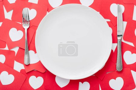 Photo for Top view of empty white plate, knife and fork on red paper cut cards with hearts symbols - Royalty Free Image