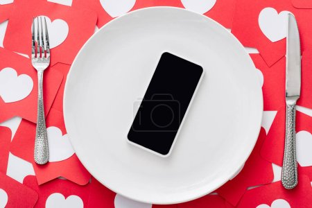 Photo for Top view of smartphone with blank screen on white plate near knife and fork on red paper cut cards with hearts symbols - Royalty Free Image