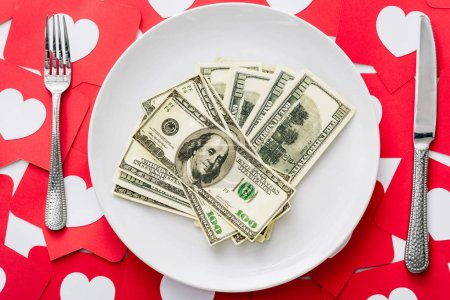 Photo for Top view of dollar banknotes on white plate near knife and fork on red paper cut cards with hearts symbols - Royalty Free Image