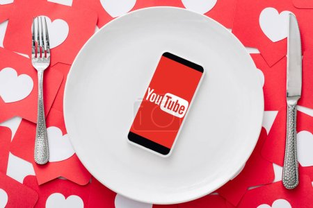 Photo for Top view of smartphone with youtube app on screen on white plate near knife and fork on red paper cut cards with hearts symbols - Royalty Free Image