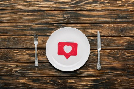 Photo pour Top view of white plate with red paper cut card with heart symbol near knife and fork on brown wooden surface - image libre de droit