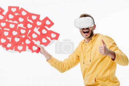 Photo pour Homme excité dans le casque virtuel de réalité affichant le pouce vers le haut tout en retenant les cartes coupées de papier rouge avec des symboles de coeurs isolés sur le blanc - image libre de droit