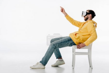 Photo for Side view of man in virtual reality headset sitting on chair and pointing with finger on white background - Royalty Free Image