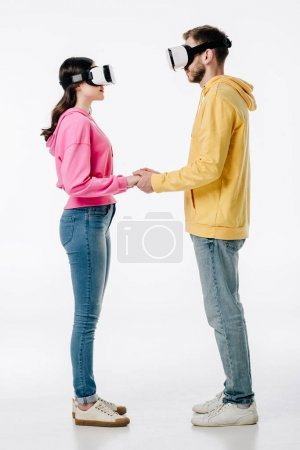 Photo pour Young man in woman in blue jeans and hoodies holding hands while using virtual reality headsets on white background - image libre de droit