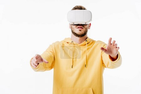 Photo for Front view of young man in yellow hoodie using virtual reality headset isolated on white - Royalty Free Image