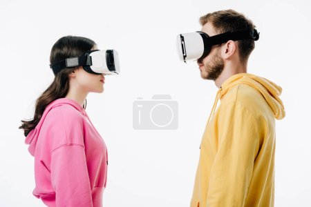 Photo for Side view of young man and woman using virtual reality headsets isolated on white - Royalty Free Image