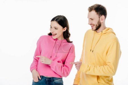 Photo for Young cheerful man and woman in hoodies pointing with fingers and looking away isolated on white - Royalty Free Image