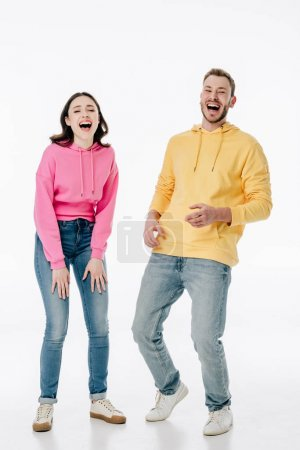 Photo pour Jeune homme et femme gai dans des jeans et des hoodies riant tout en regardant l'appareil-photo sur le fond blanc - image libre de droit
