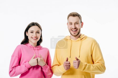 Photo for Young cheerful man and woman showing thumbs up while looking at camera isolated on white - Royalty Free Image