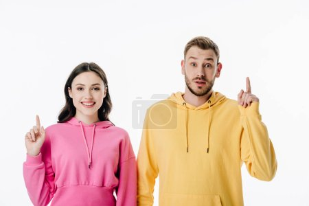 Photo pour Young smiling man and woman showing idea signs and looking at camera isolated on white - image libre de droit