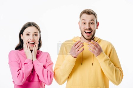 Photo for Young excited man and woman gesturing while looking at camera isolated on white - Royalty Free Image
