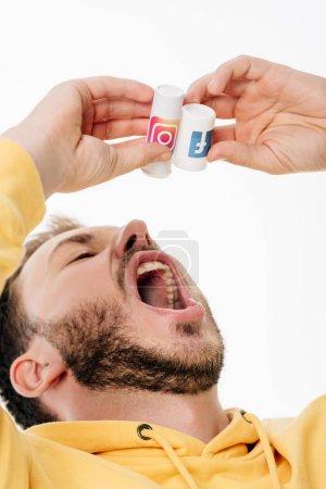 Photo pour Jeune homme barbu imitant des pilules pour avaler à partir d'un contenant avec facebook et des logos d'instagram isolés sur blanc - image libre de droit