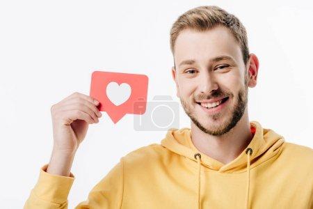 Photo pour Bel homme joyeux tenant carte de papier rouge avec symbole de coeur et regardant la caméra isolée sur blanc - image libre de droit