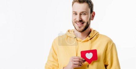 Photo pour Plan panoramique d'un jeune homme joyeux tenant un carton rouge avec le symbole du cœur et regardant la caméra isolée sur blanc - image libre de droit