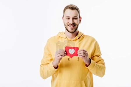 handsome cheerful man in yellow hoodie holding red paper cut card with heart symbol isolated on white