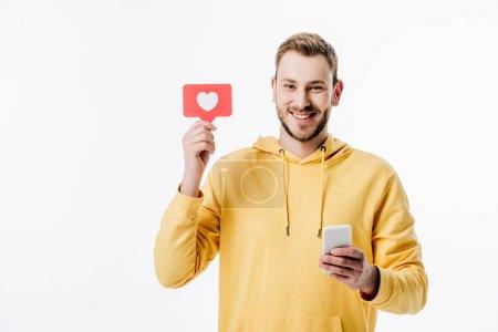 Photo pour Joyeux jeune homme en sweat à capuche jaune tenant carte de papier rouge avec symbole de coeur tout en utilisant smartphone isolé sur blanc - image libre de droit