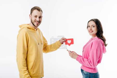 smiling handsome man giving red paper cut card with heart symbol to pretty girl using smartphone isolated on white
