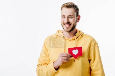 Photo pour Bel homme joyeux en sweat à capuche jaune tenant carte de coupe en papier rouge avec symbole de coeur isolé sur blanc - image libre de droit