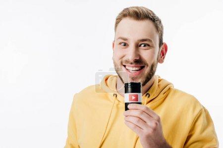 Photo pour Jeune homme excité dans le récipient de fixation jaune de hoodie avec le logo de youtube et regardant l'appareil-photo isolé sur le blanc - image libre de droit