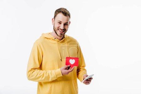 Photo pour Joyeux jeune homme à l'aide d'un smartphone tout en tenant carte de coupe de papier rouge avec symbole de coeur isolé sur blanc - image libre de droit