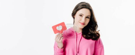 Photo pour Plan panoramique de jolie fille souriante tenant carte de papier rouge avec symbole de coeur isolé sur blanc - image libre de droit