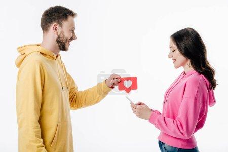 Photo pour Vue de côté de jeune homme de sourire donnant la carte rouge de coupure de papier avec le symbole de coeur à la petite amie utilisant le smartphone d'isolement sur le blanc - image libre de droit