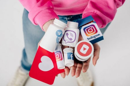 Photo for Overhead view of girl holding containers with social media logos and red paper cut card with heart symbol on grey background - Royalty Free Image