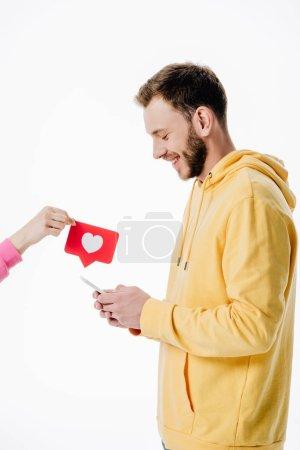 Photo pour Vue recadrée de la femme donnant carte de coupe de papier rouge avec symbole de coeur pour jeune homme en utilisant smartphone isolé sur blanc - image libre de droit