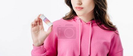 Photo for Partial view of young woman holding container with instagram logo isolated on white - Royalty Free Image