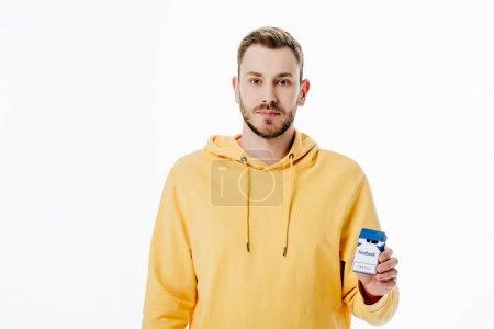 Photo pour Beau jeune homme à capuche jaune tenant paquet de cigarettes avec logo facebook isolé sur blanc - image libre de droit