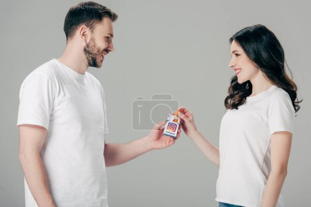 Photo for Cheerful man and woman in white t-shirts holding cigarette pack with instagram logo and looking at each other isolated on grey - Royalty Free Image