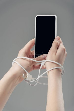 cropped view of young woman with usb cable around hands holding smartphone with blank screen isolated on grey