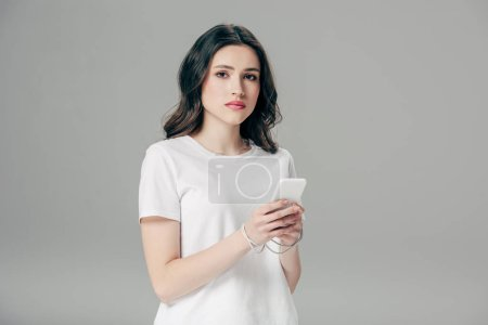Photo for Attractive young woman in white t-shirt and usb cable around hands using smartphone isolated on grey - Royalty Free Image