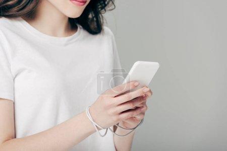 Photo pour Vue recadrée de jeune femme dans le t-shirt blanc et le câble d'usb autour des mains utilisant le smartphone isolé sur le gris - image libre de droit