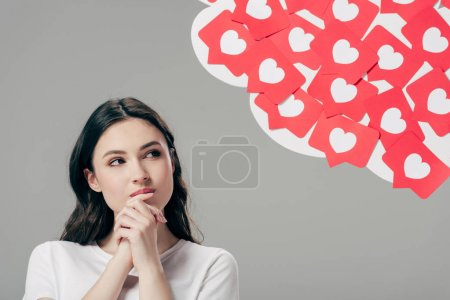 Photo for Pretty dreamy girl looking at red paper cut cards with hearts symbol isolated on grey - Royalty Free Image