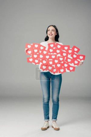 Photo pour Belle fille de sourire dans des jeans retenant les cartes coupées rouges de papier avec le symbole de coeur sur le fond gris - image libre de droit