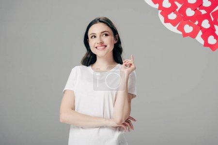 Photo pour Jolie jeune fille affichant le signe d'idée et regardant vers le haut près des cartes coupées de papier rouge avec le symbole de coeurs isolé sur le gris - image libre de droit