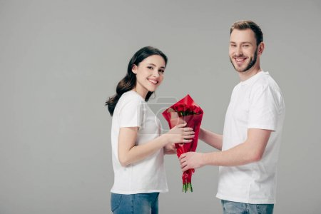 Photo for Cheerful man and woman in white t-shirts holding bouquet of red roses and looking at camera isolated on grey - Royalty Free Image