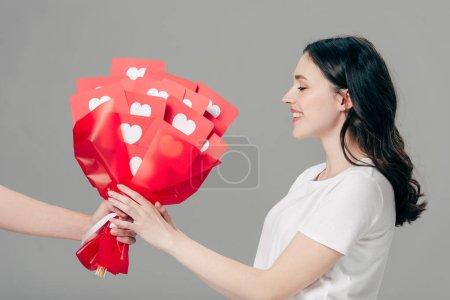 Photo pour Vue partielle du bouquet de cadeau d'homme des cartes coupées de papier rouge avec des symboles de coeur à la jolie fille d'isolement sur le gris - image libre de droit